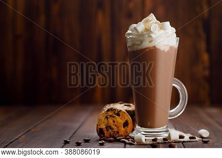 Glass Of Frappe With Whipped Cream Topping And Cookies On Wooden Table