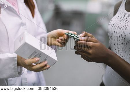 Cropped Image Of Hands Of Woman Pharmacist Holding Box With Drug And Giving Blister With Pills To Bl
