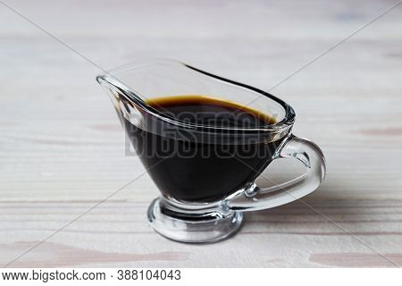 Soy Sauce In A Glass Gravy Boat On A White Wooden Background. Dish Of Soy Sauce On White Wooden Tabl