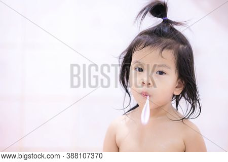 Adorable Asian Girl Is Standing, Taking A Shower And Brushing Her Teeth In Bathroom With A Bright Wh