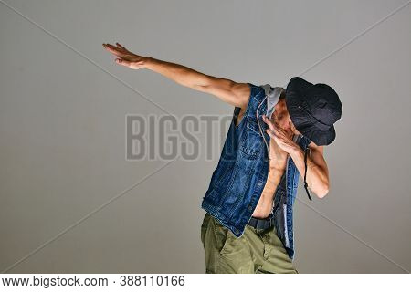 Young Guy Breakdancer In Hat Dancing Dab In Studio Isolated On Gray Background. Dance School Poster