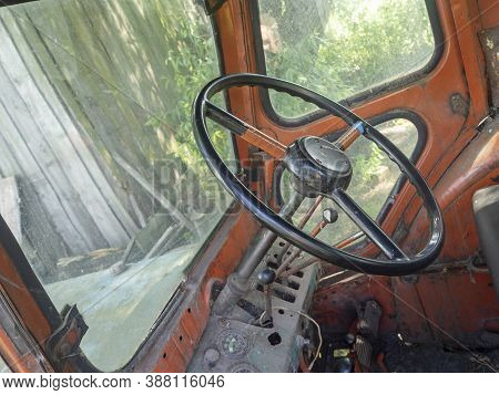 View Of The Cab Of An Old Tractor. Steering Wheel And Interior Of The Cab. Agricultural Machinery, S