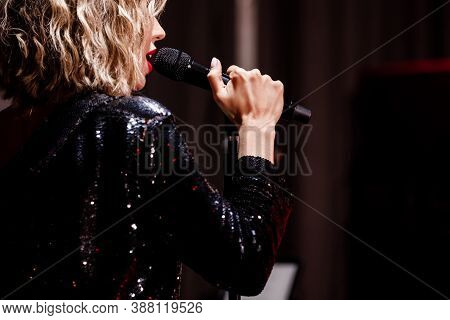 Girl Singer With Microphone Singing And Dancing Over Holiday Glowing Background. Karaoke Singer. Dis