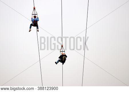 Couple On The Zipline On Sky Background, Bottom View