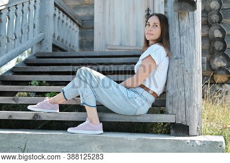 Pretty Woman Sitting On A Stairs Of Old Abandoned Wooden House. Country Travelling. Woman Wearing Ca