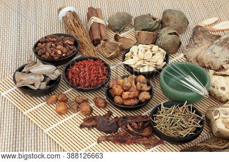 Traditional Chinese herbal medicine with acupuncture needles & herb & spice selection on bamboo. Alternative health care concept.
