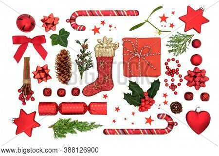Christmas composition with red bauble decorations, winter holly, ivy, mistletoe, fir & gift related symbols on white background. Xmas theme for the festive season. Flat lay, top view.