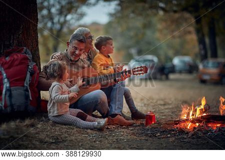 Grandparents singing with grandchildren on camping; Quality family time concept