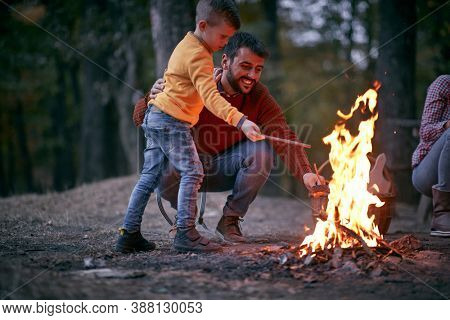 Father and son starting a fire together on a camping; Quality family time concept