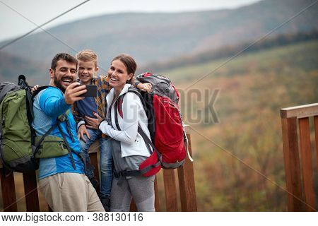 Happy couple with a son on a hiking adventure;Spring or autumn hiking in nature; camping, travel, tourism,lifestyle,  hike and people concept. Quality active family time together.
