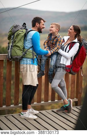 Happy couple with a son on a hiking adventure; Spring or autumn hiking in nature; camping, travel, tourism,lifestyle,  hike and people concept. Quality active family time together.