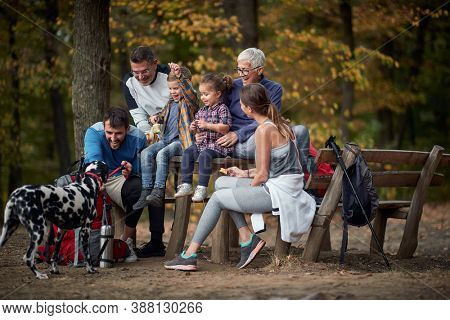 Happy family with a dog having a picnic together in the woods ; Spring or autumn hiking in nature; camping, travel, tourism,lifestyle,  hike and people concept. Quality active family time together.