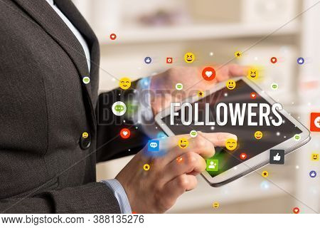 Close up of business person playing multimedia with social media icons and FOLLOWERS inscription