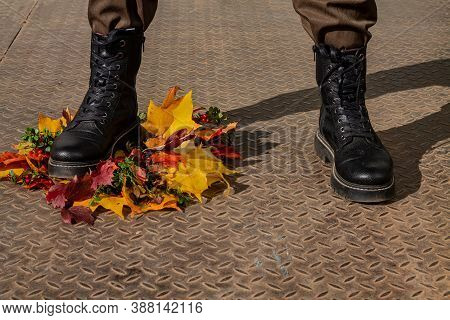 The Feet Of A Man In Berets Who Stepped On A Beautiful Wreath Of Autumn Leaves. Symbol - Aggressor,