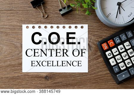 C.o.e Center Of Excellence. Text On White Paper On Wood Background Near Calculator, Paper Clips, Ala