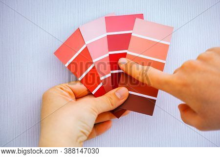 Woman Choosing Red Colour From Color Swatches Against Wall.