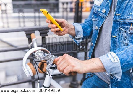 Close Up Of Man Using Phone Outdoors. Man Sitting On Bike Using Cellphone . Lifestyle Concept.