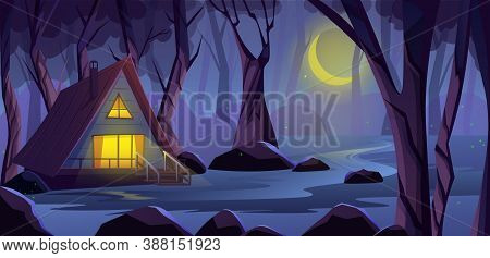 Wooden Cottage House In The Night Forest, On The Edge Of A Swamp. Light In The House Windows, Wooden