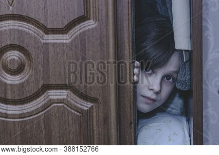 Child Scared Of Nightmare And Hiding In Closet. Ghost Of Little Girl Hid In Cupboard At Dark Night.