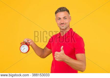 He Is Always Punctual. Punctual Man Hold Alarm Clock Showing Thumbs Up. Happy Being On Time. Precise