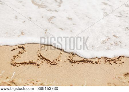 Good Bye 2020 ! Wave With Foam Covering 2020 Sign On Sandy Beach, Leaving Awful Year 2020