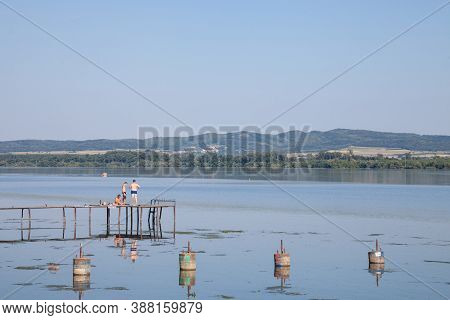 Dubovac, Serbia - August 3, 2017: Young Men, Serbs, Swimming From An Old  Pontoon On The Danube Rive