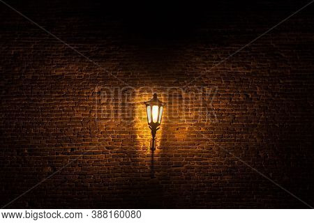 Vintage Old Street Lantern Lit With An Orange Light In Front Of A Brick Wall During A Gloomy Dark Ni