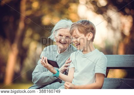 Young Boy And His Great Grandmother Using Smartphone To Makie Video Call Or Take Selfie. Streaming O