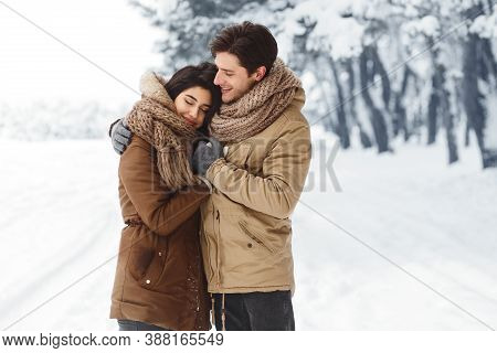 Winter Morning Date. Sweet Couple Hugging Standing In Snowy Forest Walking Outdoor