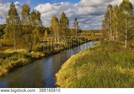 Autumn Landscape With Birches, River, Blue Sky And Clouds.