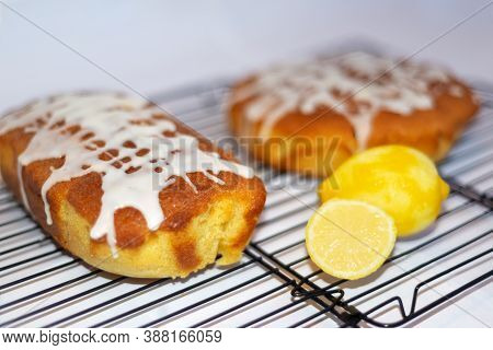 Side View Of Two Freshly Baked Home Made Lemon Drizzle Cakes With Criss Cross Icing And Cut Lemon At