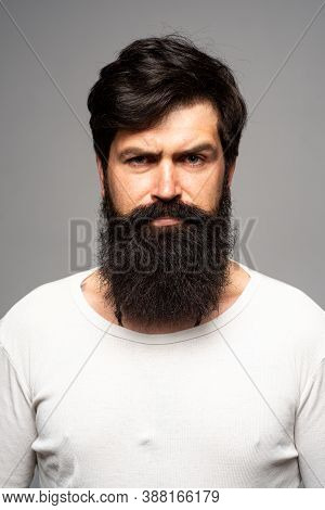 Portrait Of Confident Serious Man Has Beard And Mustache, Looks Seriously, Isolated. Thinking Stylis