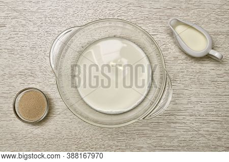 The Stage Of Preparation Yeast Dough. Transparent Pan With Milk. Next To The Yeast And Creamer. On A