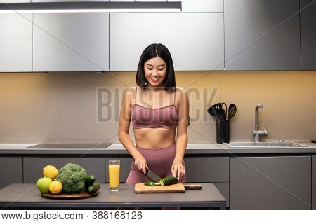 Slim Chinese Lady Cooking Healthy Vegetable Salad In Modern Kitchen, Preparing Dinner For Weight Los
