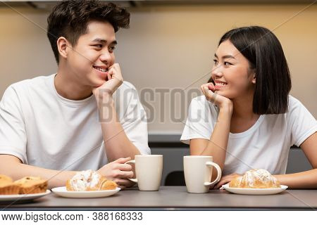 Loving Korean Couple Drinking Morning Coffee And Eating Breakfast With Croissants Sitting In Kitchen