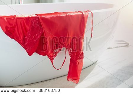Luxurious Satin Nightgown And Robe In Red Hung On The Bathtub In The Bathroom In The Morning.