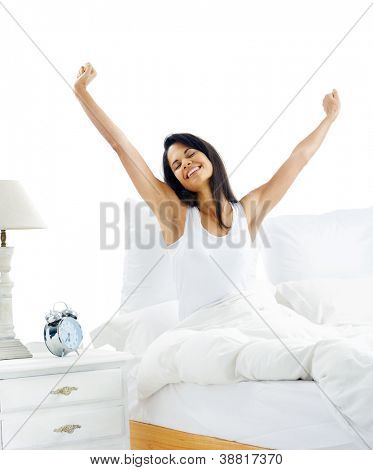 Tired sleepy woman waking up and yawning with a stretch while sitting in bed isolated on white background