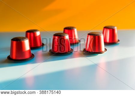 A Lot Of Red Capsules Coffee Open Composition On Blue And Orange Background, Flat Lay. Coffee Pod Ca