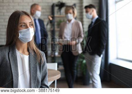 Businesswoman In Medical Mask With Her Staff, People Group In Background At Modern Bright Office Ind