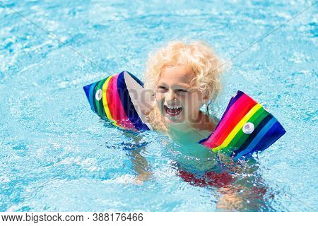Child In Swimming Pool Wearing Colorful Inflatable Armbands. Kids Learn To Swim With Float Aid. Floa