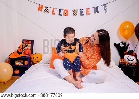 Mother With Daughter In Costume For Celebrating Halloween At Home. Kid With Mom In Bedroom Decoratio