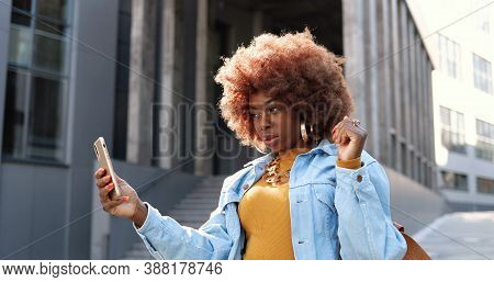 Beautiful Young African American Curly Woman Posing To Smartphone Camera While Taking Selfie Photo A