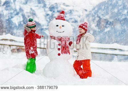 Child Building Snowman. Kids Build Snow Man. Boy And Girl Playing Outdoors On Snowy Winter Day. Outd