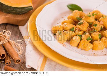 Pumpkin Gnocchi With Grated Amaretti Cookies On White Dish.