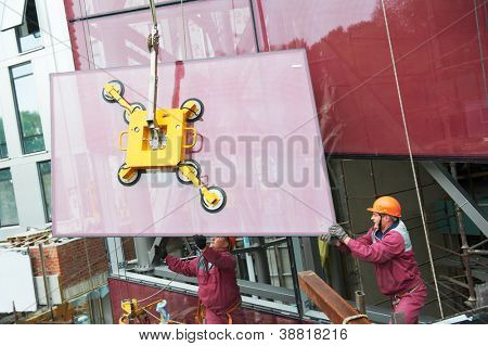 Tho builders worker installing glass windows on facade of business building poster