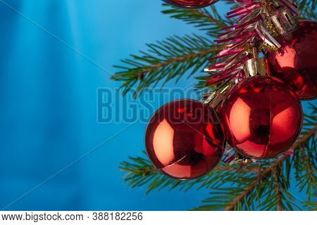 Christmas Card With Red Balls On A Spruce Branch