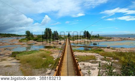 Little wooden bridge in a bay at low tide in north coast in Quebec named Johan-Beetz with a cloudy blue sky