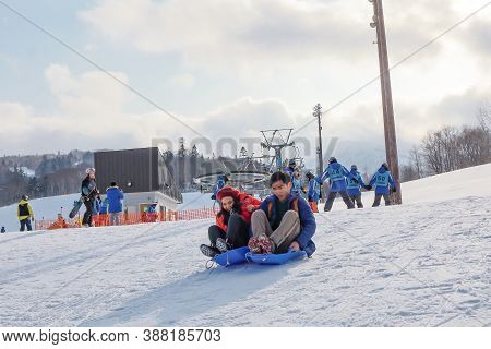 Hokkaido, Japan - December 2019 : Photo Of Love Couple Are Playing Ski Sliders Together In The Mount