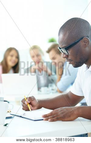 Portrait of cute African guy planning work with group of partners on background