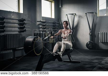 Female in White Sportswear Has Training on Rowing Machine .